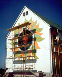 Frank Boggs painting the sunburst on the side of the barn.