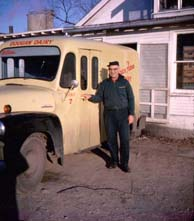 A photo of a milkman in front of his milk truck.