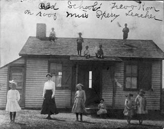 vintge photo of children standing in front of, and on the roof of, old schoolhouse